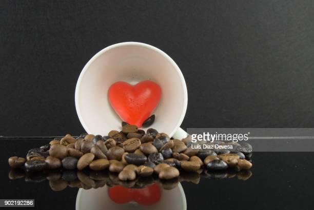 porcelain cup with roasted coffee beans with heart inside - heart internal organ stock pictures, royalty-free photos & images