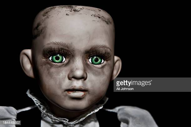 CONTENT] A porcelain doll with a dirty face piercing green eyes and no hair looks into the camera