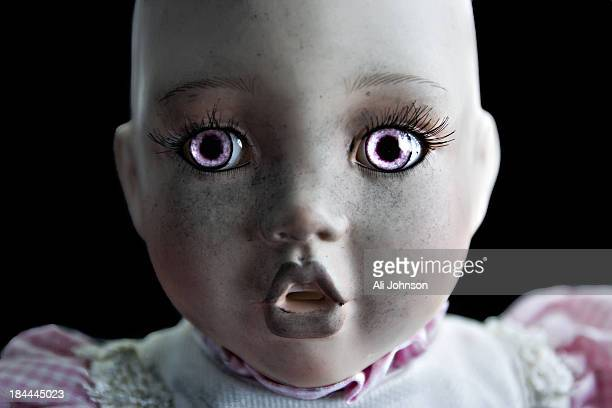 CONTENT] A porcelain doll with pink eyes no hair and a dirty face looks into the camera