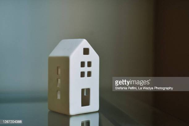 porcelain house shape on a glass table. conceptual with space for copy. - loan stock pictures, royalty-free photos & images