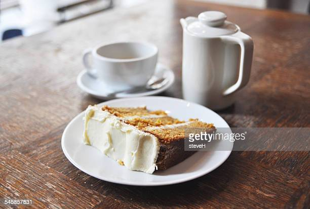 Porcelain teapot, cup, and plate with carrot cake on wooden table in bar