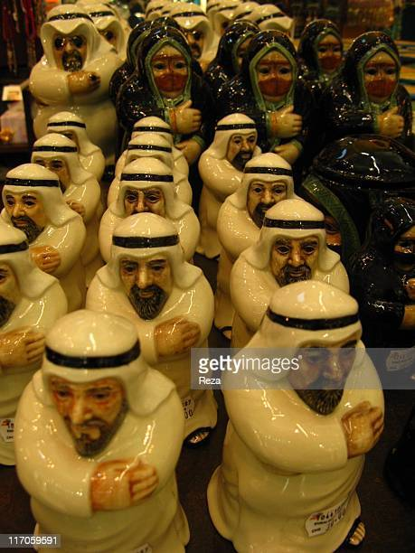 Porcelaine figurines sold in a duty free shop inside the airport May 24 2009 in the Dubai International Airport The men are wearing traditional Arab...