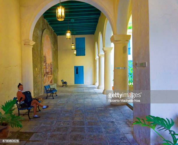 Porch of a Colonial building it has stone flooring light yellow walls round pillars with archways sitting benches also there
