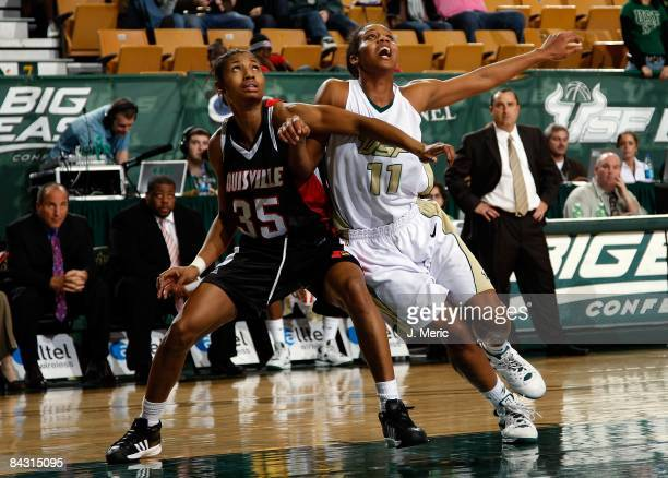 Porche Grant of the South Florida Bulls battles for a rebound with Angel McCoughtry of the Louisville Cardinals during the game at the SunDome on...