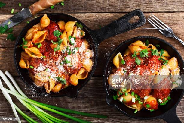 Pork and beef baked meatballs with pasta served in rustic cast iron pans