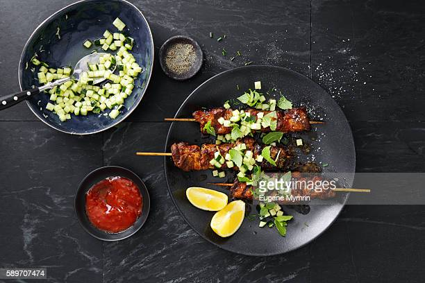 Pork belly skewers with cucumber salad