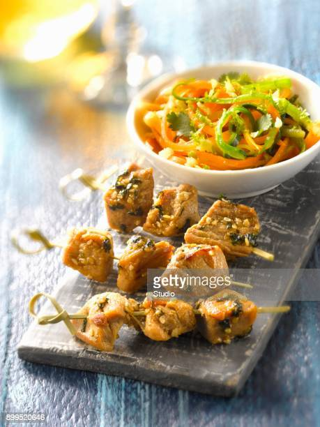 Pork brochettes marinated in soya sauce and vegetable strips in citrus fruit juice