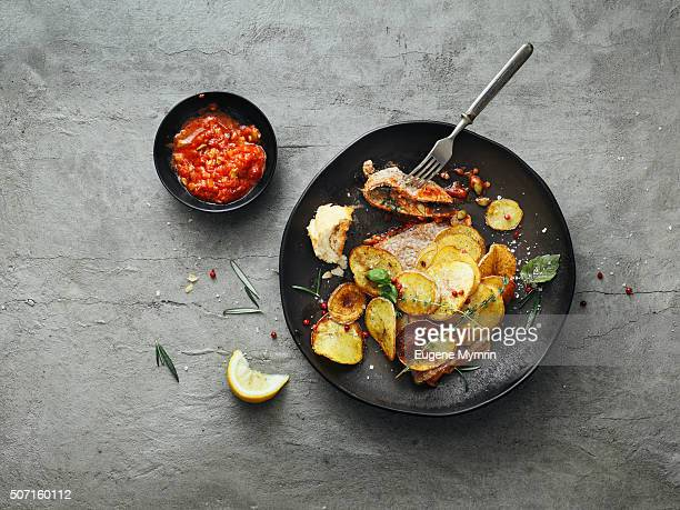 Pork chop with potato chips and tomato sauce