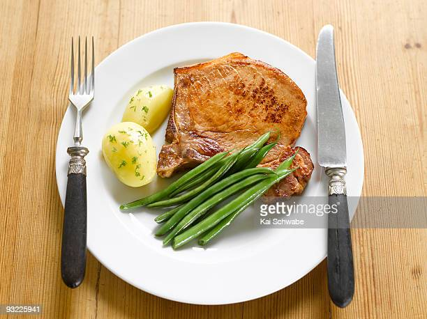 pork chop with potatoes and green beans on plate - bush bean stock photos and pictures