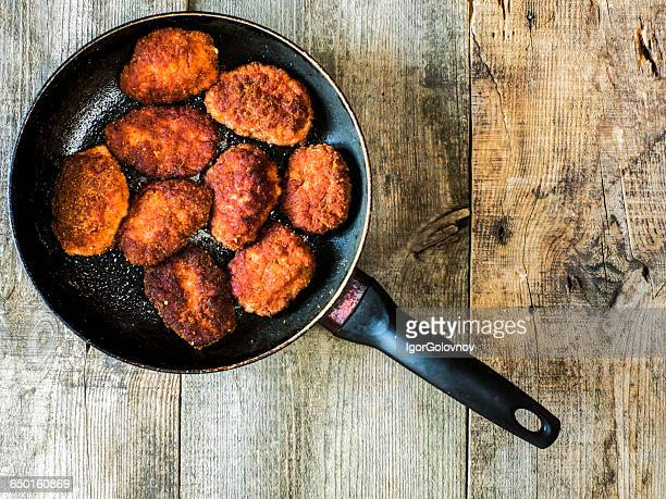 Pork cutlets fried in breadcrumbs in frying pan
