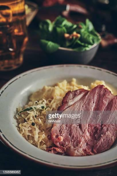 varkensknokkel met zuurkool en aardappelpuree - zuurkool stockfoto's en -beelden