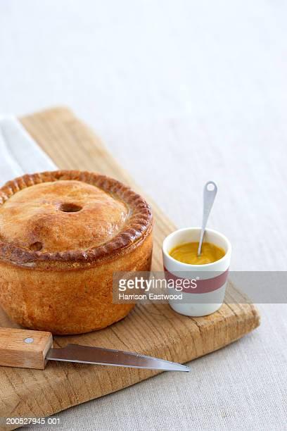 Pork pie with mustard on chopping board