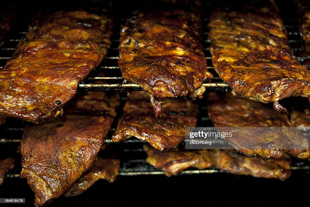 Pork ribs cook in a smoker at a Famous Dave's of America Inc. franchise restaurant in Peoria, Illinois, U.S., on Thursday, March 21, 2013. Famous Dave's of America is a chain of barbecue restaurants started in 1994 that has 191 locations in 34 U.S. states and one Canadian province. Photographer: Daniel Acker/Bloomberg via Getty Images