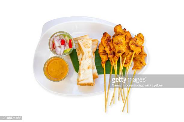 pork satay with coconut milk and bread with sauce in white plastic plate on a white background. - plastic plate stock pictures, royalty-free photos & images