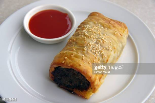 Pork sausage roll served on a white plate with a dipping bowl of tomato sauce