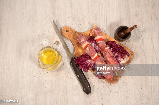 Pork skewers. Extra virgin olive oil and oregano. Before cooking. Italy. Europe.