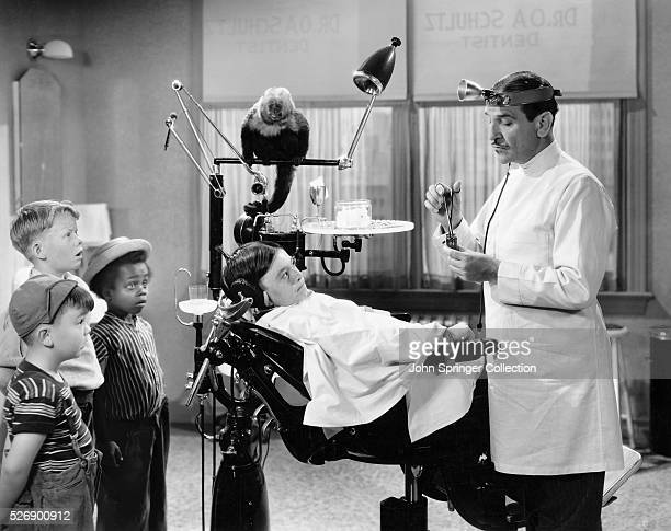 Porky Spike and Buckwheat look on as Dr Schultz prepares to work on Alfalfa From the 1938 short film The Awful Tooth