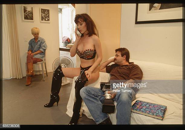 A porn actress talks on the phone on the set of an adult movie shoot as film crew sit by
