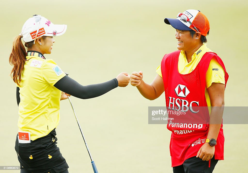 Pornanong Phatlum of Thailand celebrates a birdie putt on the 18th green with her caddie during the second round of the HSBC Women's Champions at Sentosa Golf Club on March 4, 2016 in Singapore.