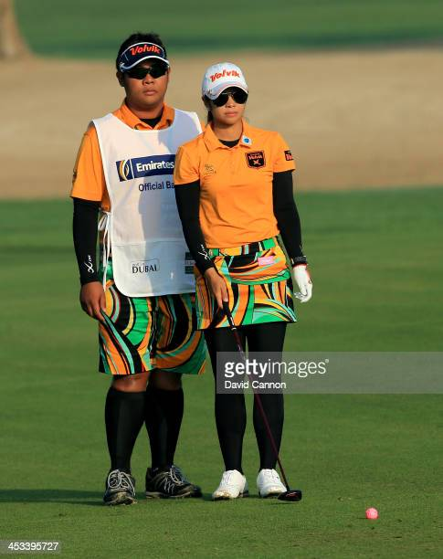 Pornanong Phatlum of Thailand waits with her caddie before hitting her second shot on the par 5, 10th hole during the first round of the 2013 Omega...