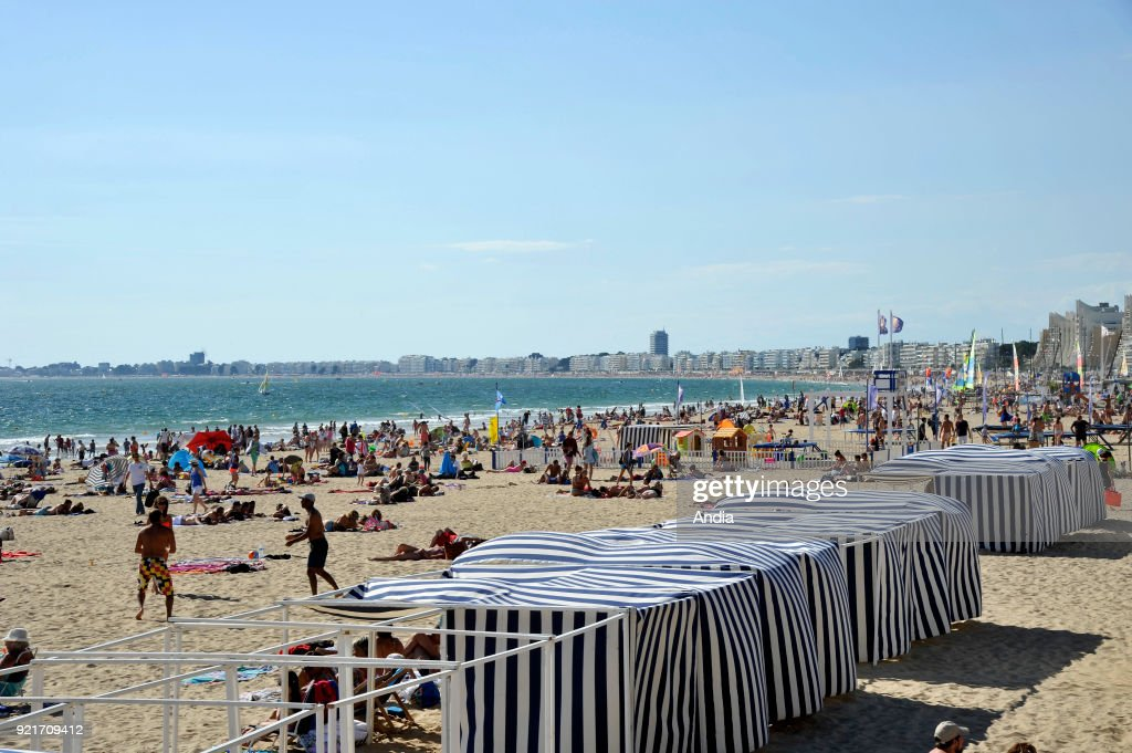 'plage des Libraires' beach in summer and the bay of La Baule in the background with buildings along the waterfront. Holiday-makers on the beach and blue and white striped beach huts.
