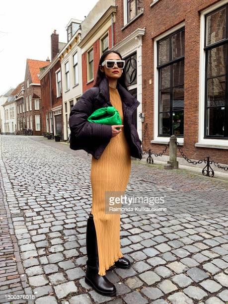 Pornwika Spiecker wearing Holzweiler dress and jacket, Ann Demeulemeester boots, Bottega Veneta bag and Celine sunglasses poses during an online...