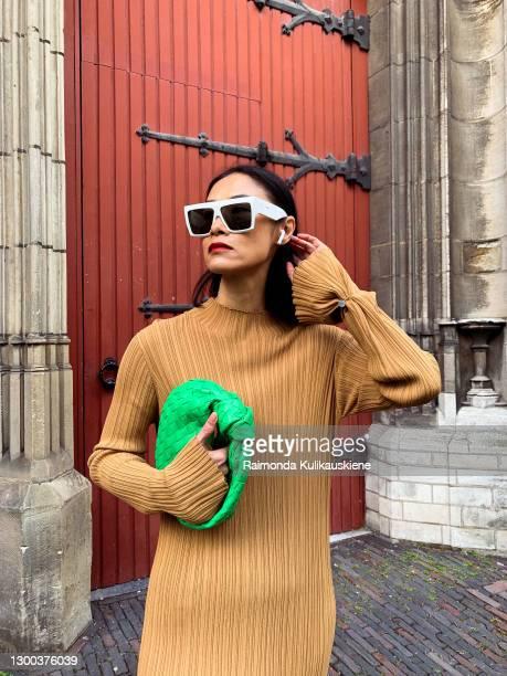 Pornwika Spiecker wearing Holzweiler dress, Ann Demeulemeester boots, Bottega Veneta bag and Celine sunglasses poses during an online street style...