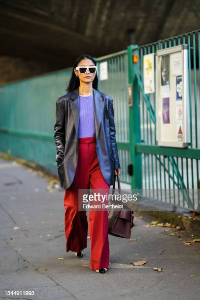 Pornwika Spiecker wears gold earrings, white sunglasses, a purple ribbed t-shirt, a black shiny leather long blazer jacket, high waist red large...