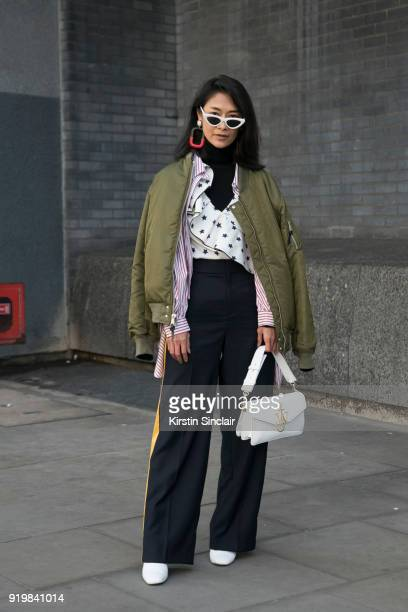 Pornwika Spierker wears a We Concept jacket Les Specs sunglasses JW Anderson bag Self Portrait top Mango trousers Kurt Geiger shoes on day one of...