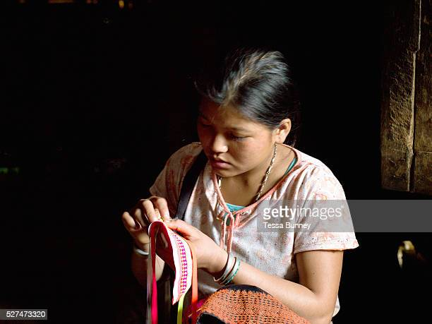 Porpae an unmarried Ko Pala ethnic minority girl sews her traditional costume at home Ban Honglerk Phongsaly Province Lao PDR One of the most...
