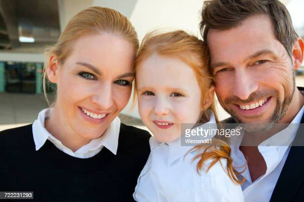 Porrait of smiling businessman and businesswoman with girl