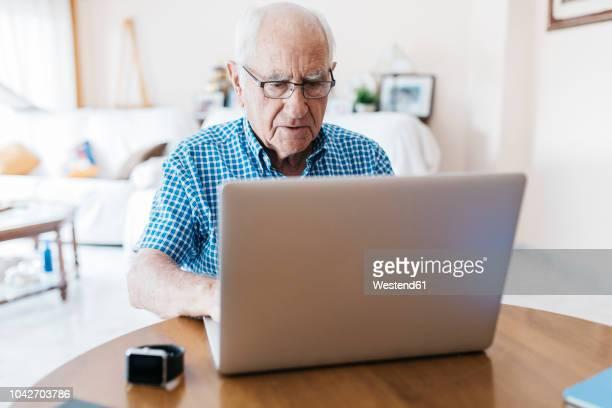 porrtait of senior man at home learning to use laptop - hombres mayores fotografías e imágenes de stock