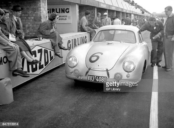 A porsche 356 coupe in the pits at Silverstone 1953