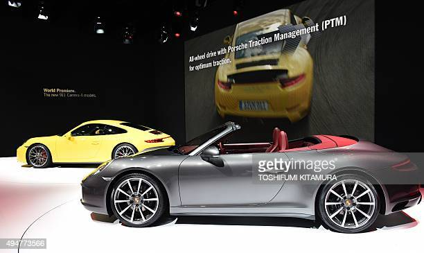 A Porsche 911 Carrera 4S and a 911 Carrera 4S Cabriolet are displayed after their premieres at the Tokyo Motor Show in Tokyo on October 29 2015 The...