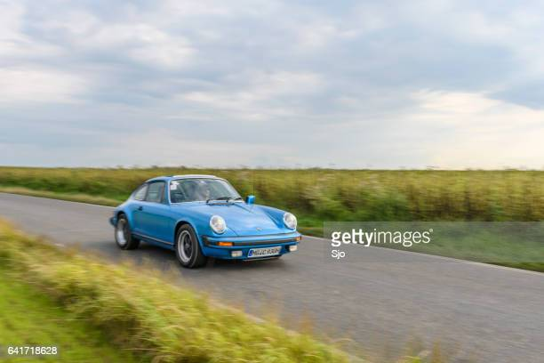 porsche 911 classic sports car driving on a country road - 1970s muscle cars stock pictures, royalty-free photos & images