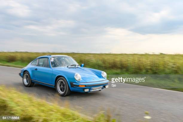 porsche 911 sport-oldtimer fahren auf einer landstraße - porsche 911 stock-fotos und bilder