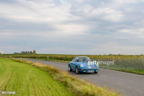 Porsche 911 classic sports car driving on a country road