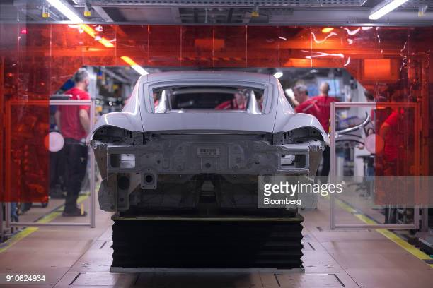 A Porsche 911 luxury automobile chassis stands on a hydraulic platform on the production line inside the Porsche AG factory in Stuttgart Germany on...
