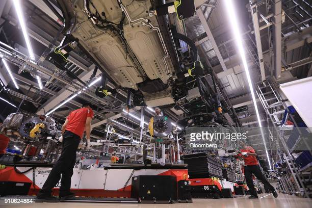 Porsche 911 luxury automobiles hang from cradles on the body and chassis assembly line inside the Porsche AG factory in Stuttgart Germany on Friday...