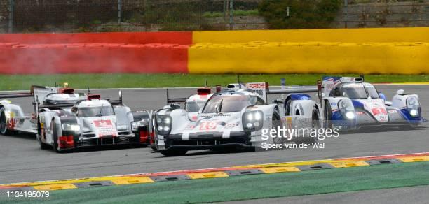 Porsche 919 Hybrid sportsprototype racing car through La Source hairpin with a second Porsche 919 and Audi R18 etron quattro following in the...