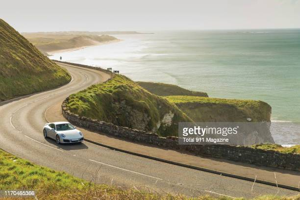 Porsche 991.2 Carrera sports car photographed driving on a coastal road through County Antrim in Northern Ireland, on April 17, 2018.