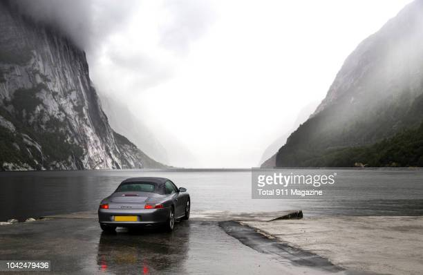 Porsche 996 Cabriolet sports car parked on the edge of a misty fjord on Norway's west coast taken on June 25 2017