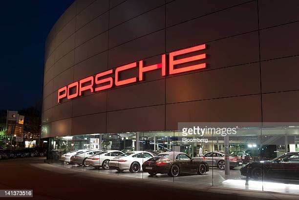 Porsche automobiles are seen illuminated at night at the Porsche plaza building in Stuttgart Germany on Thursday March 15 2012 Porsche SE the holding...