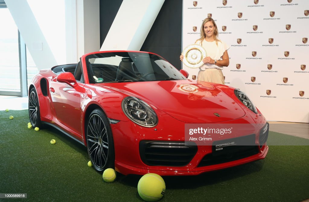 Porsche Brand Ambassador Angelique Kerber poses with the Wimbledon winner´s trophy and a Porsche 911 Turbo Cabriolet at the Porsche Museum on July 17, 2018 in Stuttgart, Germany.