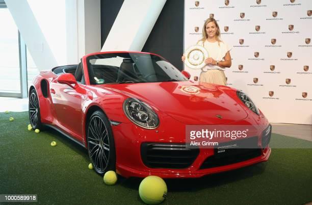Porsche Brand Ambassador Angelique Kerber poses with the Wimbledon winner´s trophy and a Porsche 911 Turbo Cabriolet at the Porsche Museum on July...