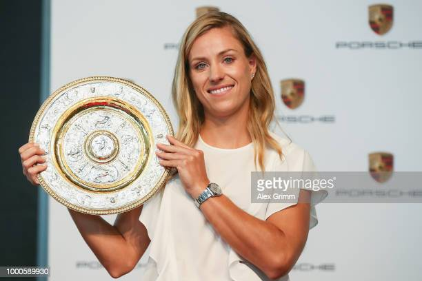 Porsche Brand Ambassador Angelique Kerber poses with the Wimbledon winner´s trophy and a Porsche 911 Turbo Cabriolet at the Porsche Museum on July...