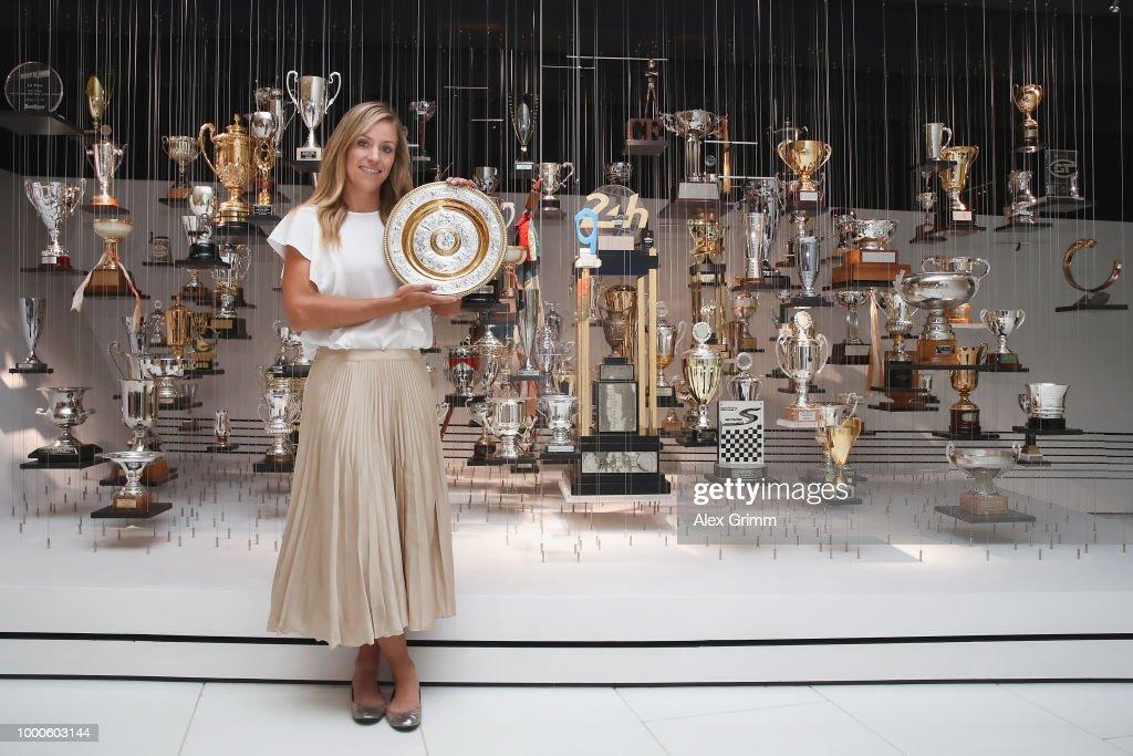 Porsche Brand Ambassador Angelique Kerber poses with the Wimbledon winner´s trophy in front of the Porsche motorsport trophy collection at the Porsche Museum on July 17, 2018 in Stuttgart, Germany.