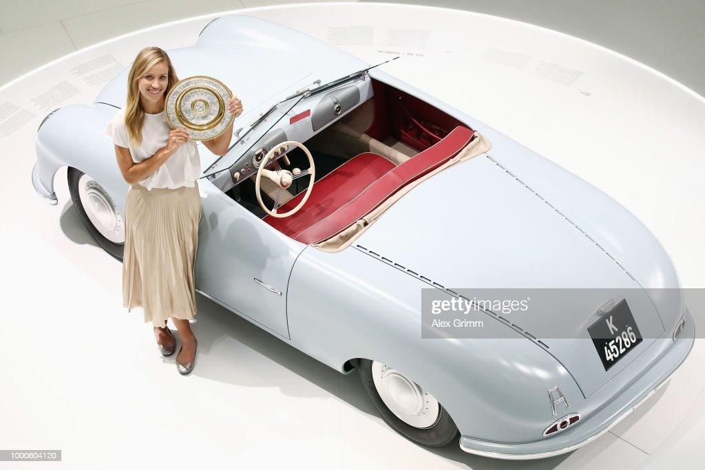Porsche Brand Ambassador Angelique Kerber poses with the Wimbledon winner´s trophy and the Porsche 356 'No 1' Roadster Show Car at the Porsche Museum on July 17, 2018 in Stuttgart, Germany.