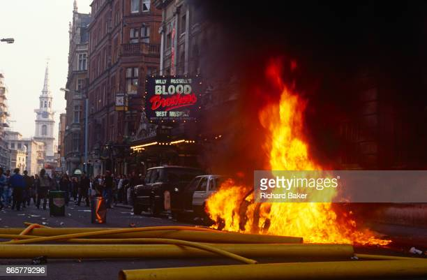 A Porsche car burns fiercely outside the theatre where Will Russel's Blood Brothers is showing during the Poll Tax riot in the UK capital on 31st...