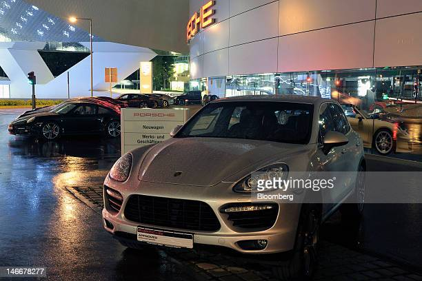 A Porsche Cayenne right and 911 automobiles stand at a dealership outside the Porsche AG plant in Stuttgart Germany on Thursday June 21 2012 Porsche...